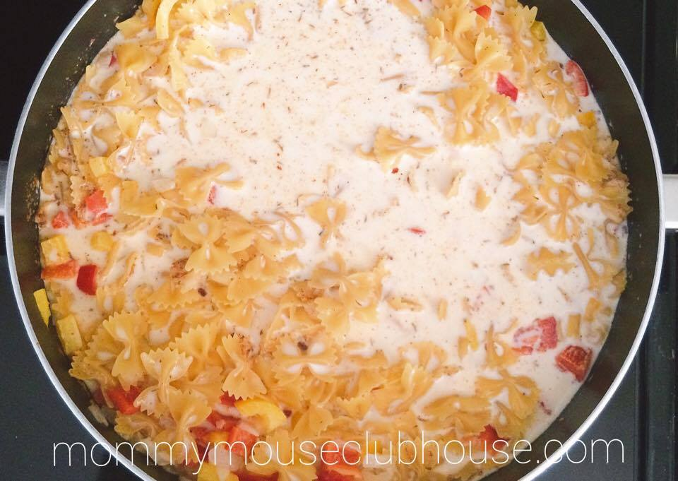 Pasta, sauce, and vegetables cooking in a frying pan to make Cheesecake Factory's Louisiana Chicken Pasta