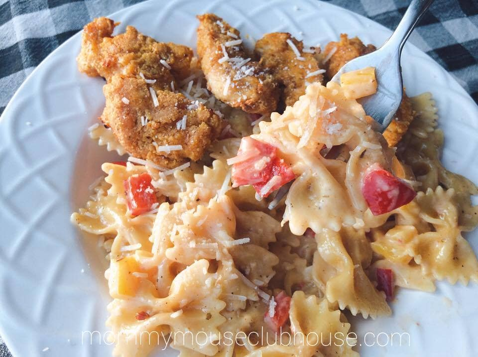 A bowl of Cheesecake Factory's Louisiana Chicken Pasta with a close up of Pasta on a fork.