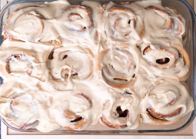 Butter Pecan Cake Mix Cinnamon Rolls with Salted Caramel Glaze in a baking dish.