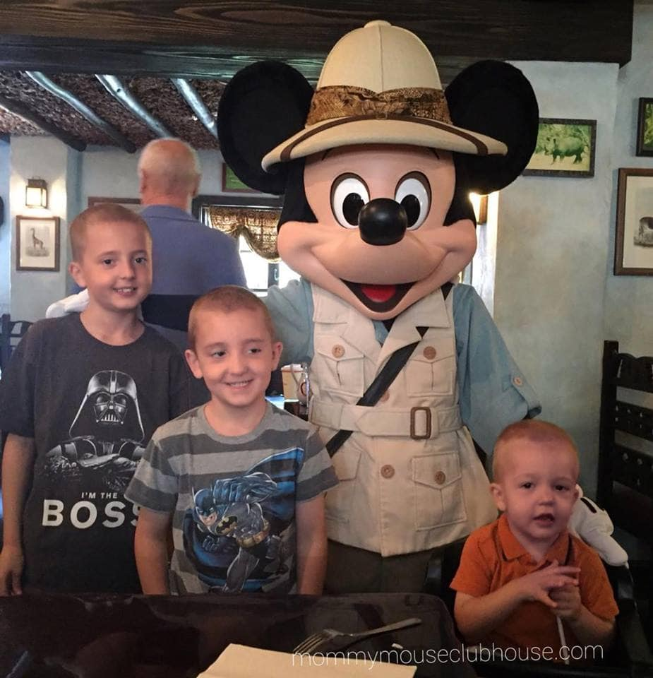 Three little boys posed with Mickey Mouse in a Safari outfit at Tusker House Restaurant.