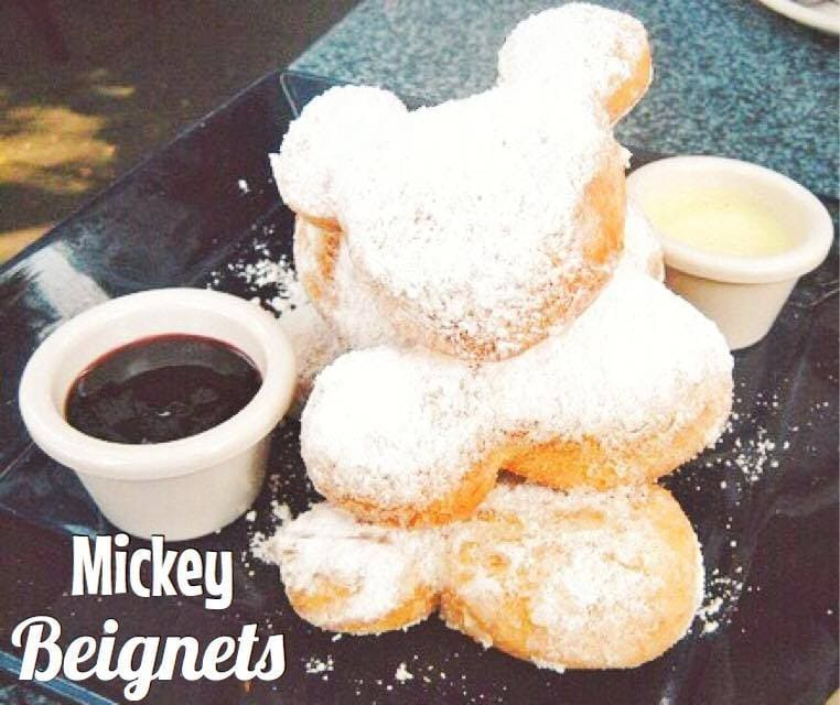 Mickey Mouse Shaped Beignets, one of the best Disney snacks, on a plate with two types of dipping sauce.