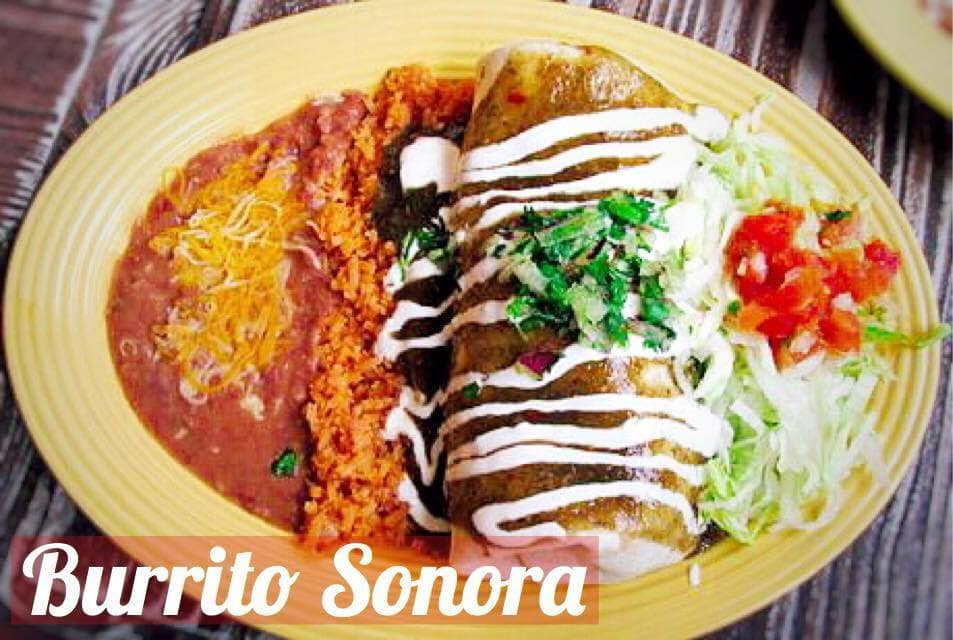 A burrito, rice, beans, lettuce, and tomato on a yellow plate on a wooden table.