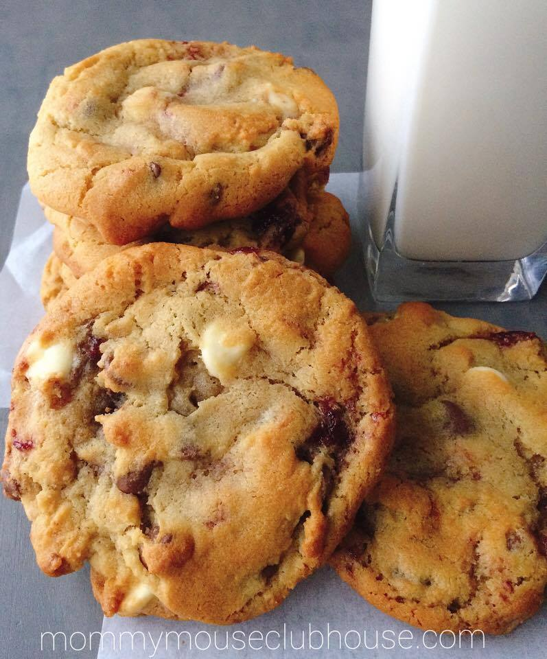 Raspberry White Chocolate Chip Cookies stacked with a glass of milk