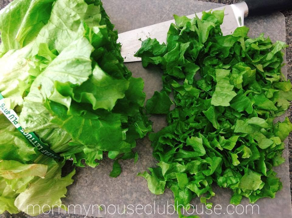 Chopped Romaine lettuce with a kitchen knife to make Barbecue Chicken Salad
