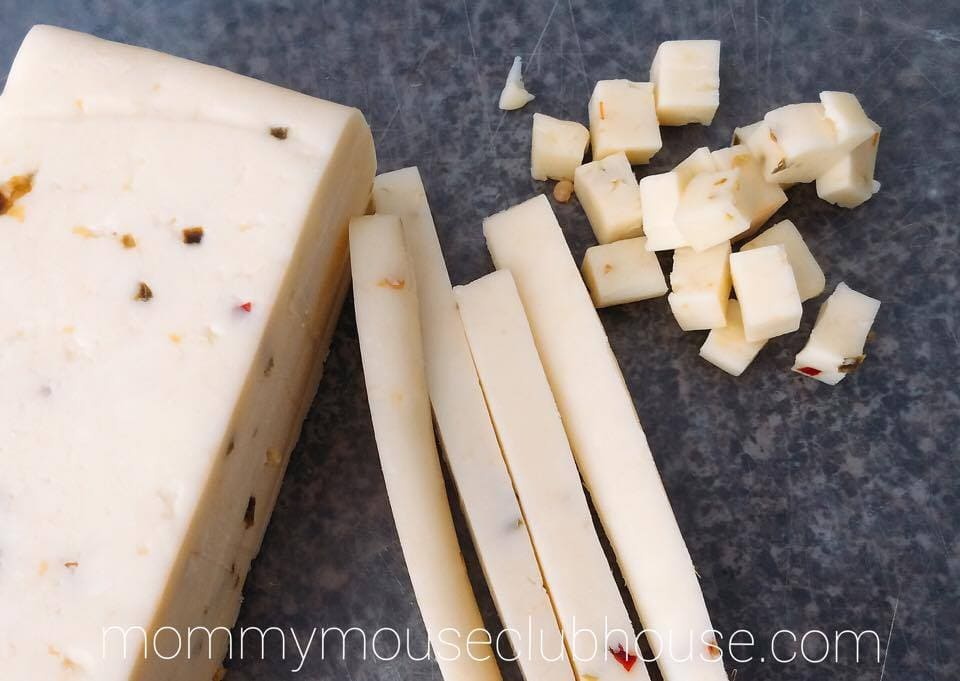 A block of Pepper Jack Cheese being diced to make Barbecue Chicken Salad