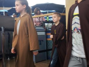 Kids wearing long brown robes are walking out to do Jedi Training at Disneyland