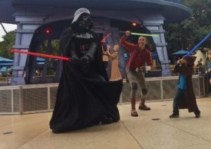 Darth Vader fighting a boy with light sabers during Jedi Training at Disneyland