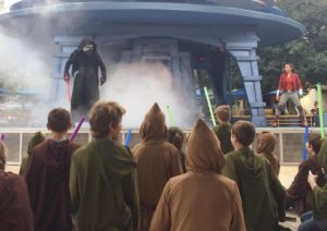 Kylo Ren on a stage with fog talking to kids with light sabers at Jedi Training at Disneyland
