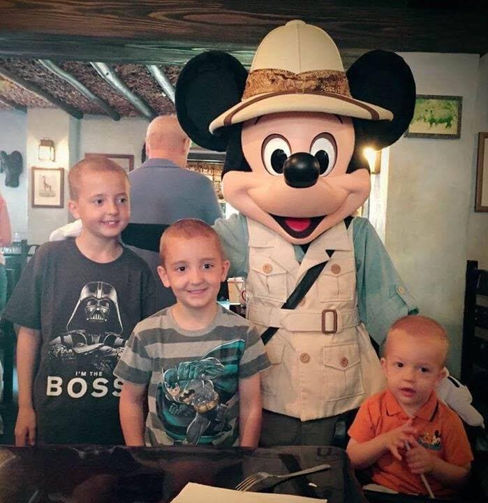 Mickey Mouse and three boys posed at Tusker House, one of The Best Disney World Character Meals