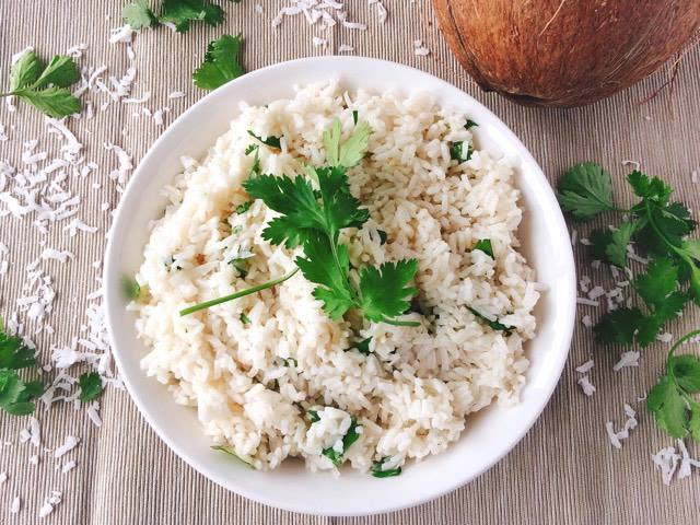 Easy Five Minute Coconut Rice in a bowl surrounded by a coconut, coconut flakes and cilantro