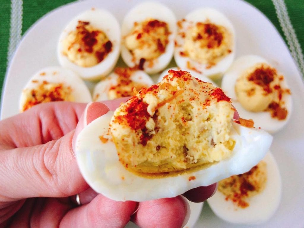 Close up picture of a Crack Deviled Eggs with a bite taken out.