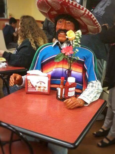 A manequin in a sombrero sitting at a table.