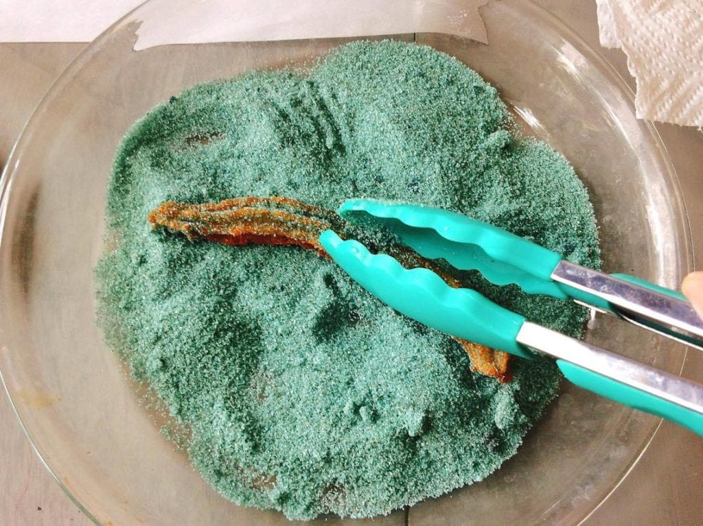 Homemade Disney Churros being dusted with blue cinnamon sugar held by blue silicone tongs.