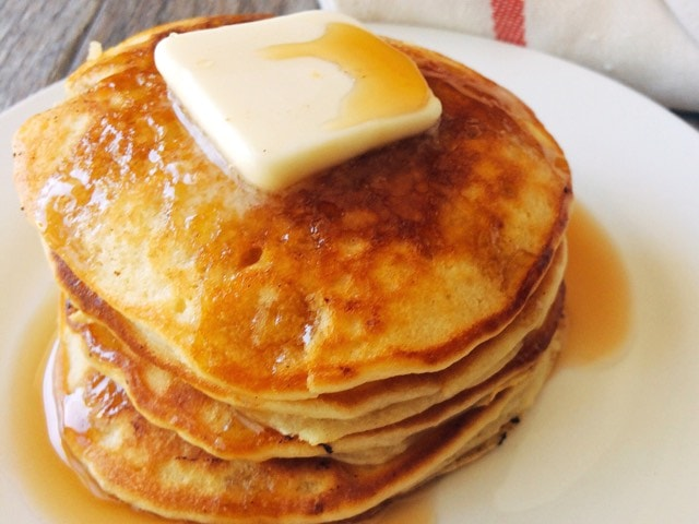 Pancakes on a white plate topped with butter and syrup.