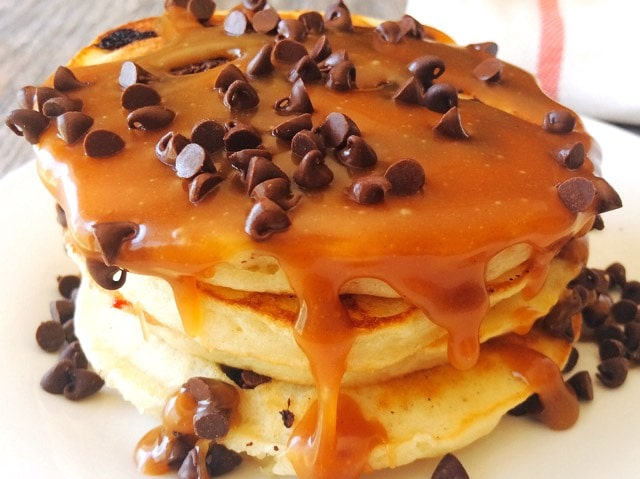 A stack of sweet cream pancakes topped with syrup and chocolate chips