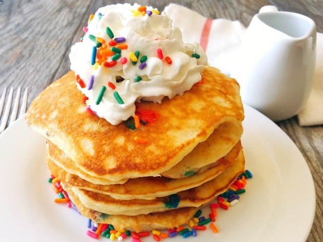 A stack of sweet cream pancakes topped with whipped cream and rainbow sprinkles.
