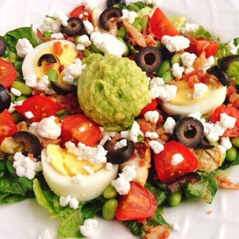 A copycat Zupas California Protein Cobb Salad with lettuce, tomatoes, olives, hard boiled eggs, avocado, and feta cheese.