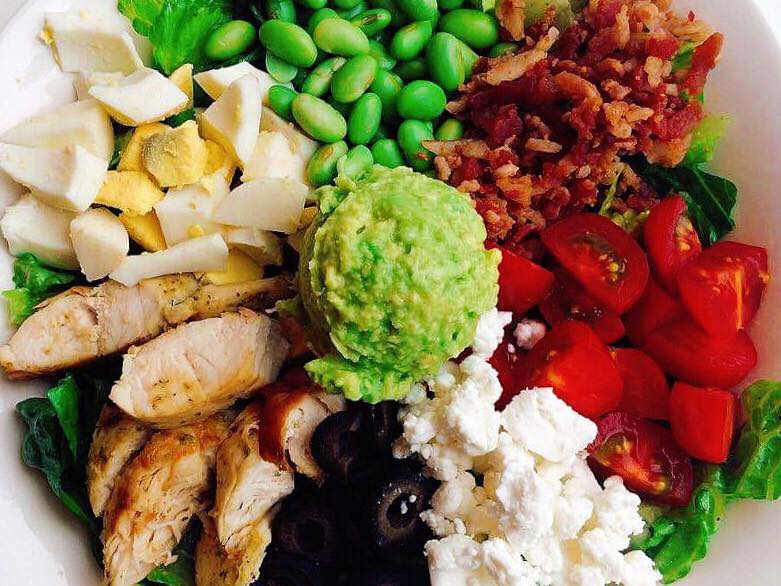 A white bowl with edamame, lettuce, bacon, tomatoes, feta cheese, avocado, black olives, chicken, and hard boiled eggs to make a Cobb salad.