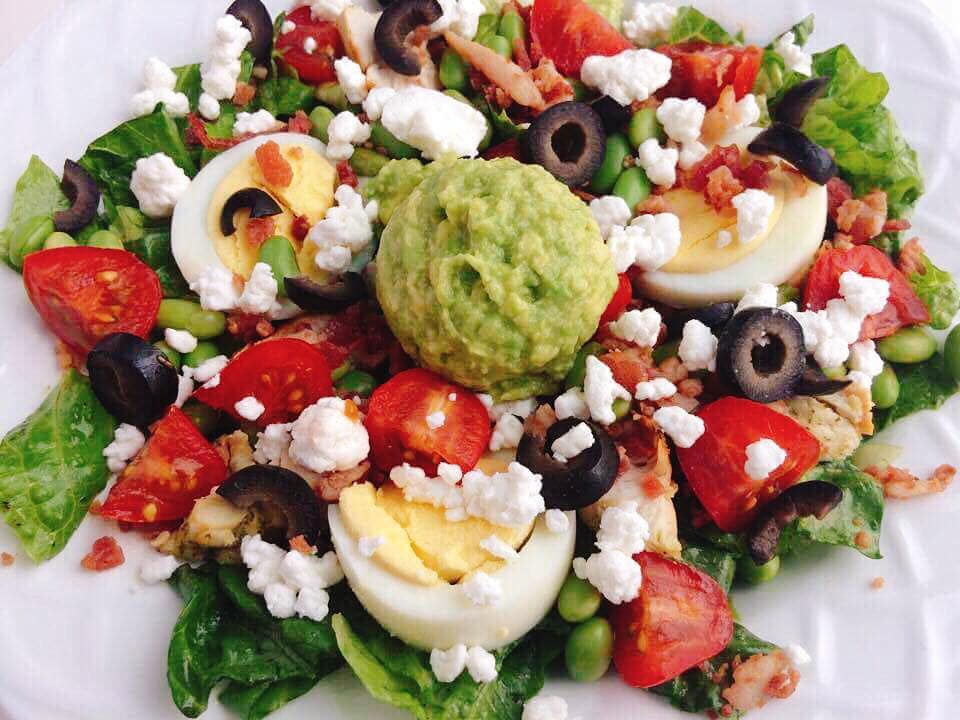 A white bowl filled with lettuce, tomatoes, olives, hard boiled eggs, avocado, bacon, and chicken to make a Cobb salad.