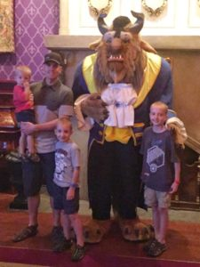 A family posed with The Beast at Be Our Guest Restaurant