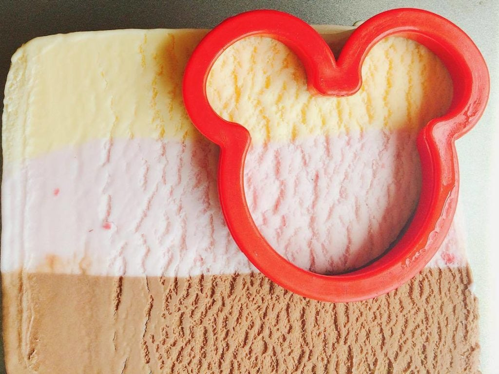 Step 3 A Mickey Mouse shaped Cookie Cutter cutting ice cream to make Homemade Hand Dipped Ice Cream Bars