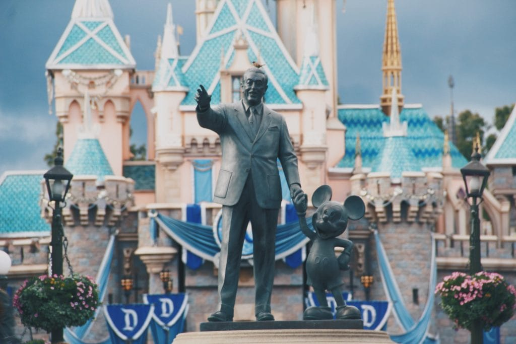Walt Disney and Mickey Mouse Statue in front of a castle at Disneyland using a Park Hopper Ticket