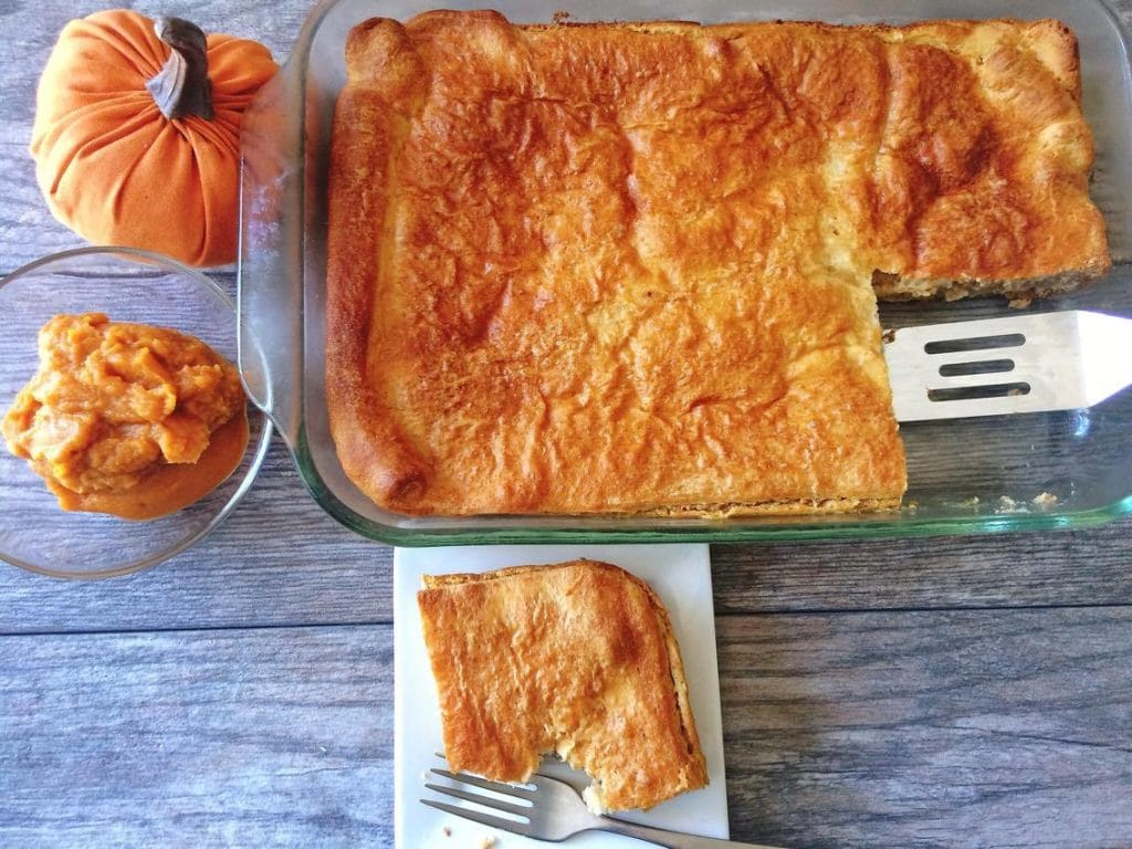 A pumpkin, pumpkin puree, a pan of pumpkin cheesecake danish and a spatula, a plate with a small slice of danish and a fork