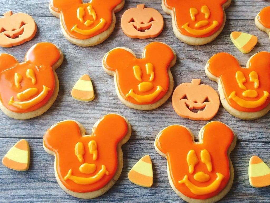 Pumpkin Spice Sugar Cookies shaped like Mickey Mouse Jack-o-lanterns with candy corns and pumpkins