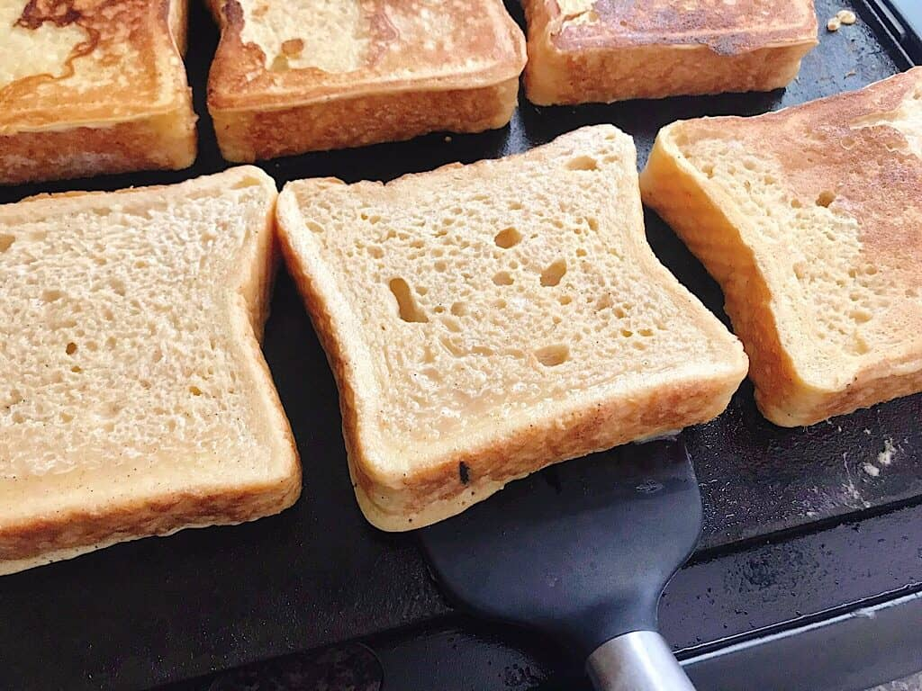 A slice of French Toast ready to be flipped over by a spatula