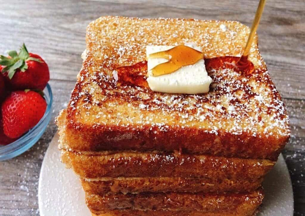 Syrup being poured on a stack of French Toast topped with a pat of butter and a side of strawberries.