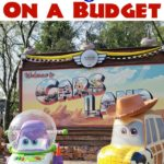 "Text ""How to Go to Disneyland on a Budget"" over a picture of two cars at Cars Land in Disneyland."