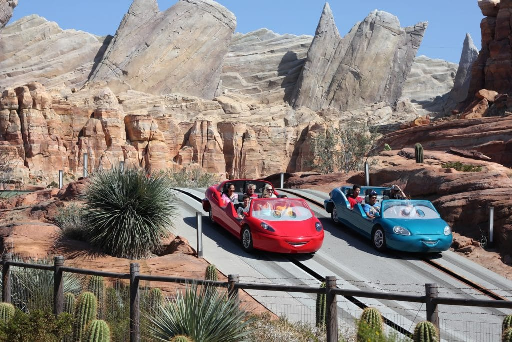 Two cars racing down the track of Radiator Springs Racers with tips to help you stay on your Disneyland Budget