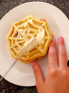 A child's hands spreading butter on a waffle to make Grilled Sweet Berry Waffle Sandwich