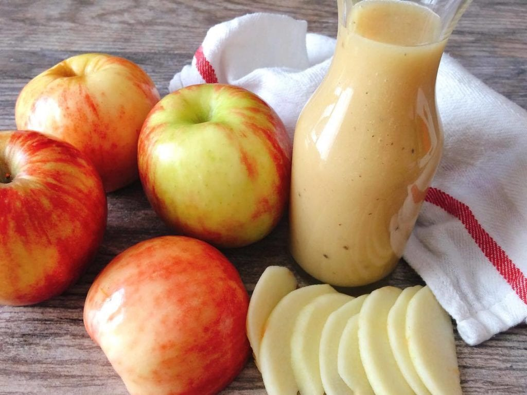 A jar of salad dressing surrounded by apples and a kitchen towel to make Honeycrisp Harvest Salad
