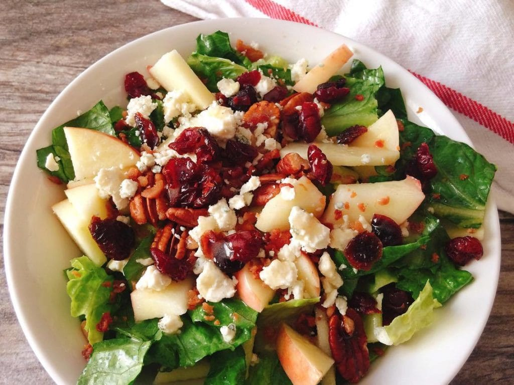 Honeycrisp Harvest Salad in a white bowl with a wood background and a kitchen towel
