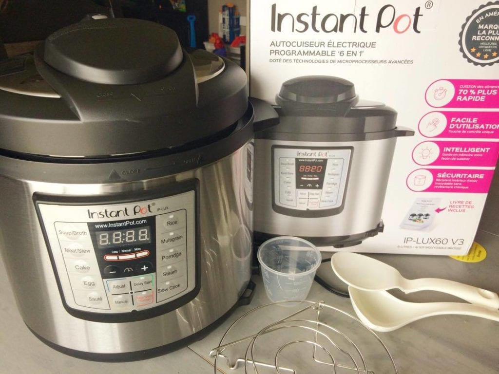 An Instant Pot and accessories next to an Instant Pot box.