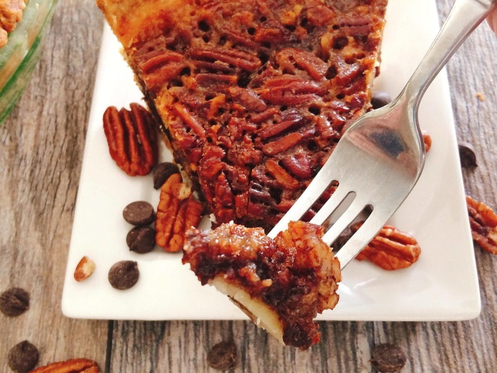 Flaky All-Butter Pie Crust as the base of a dark chocolate pecan pie on a plate with a fork.