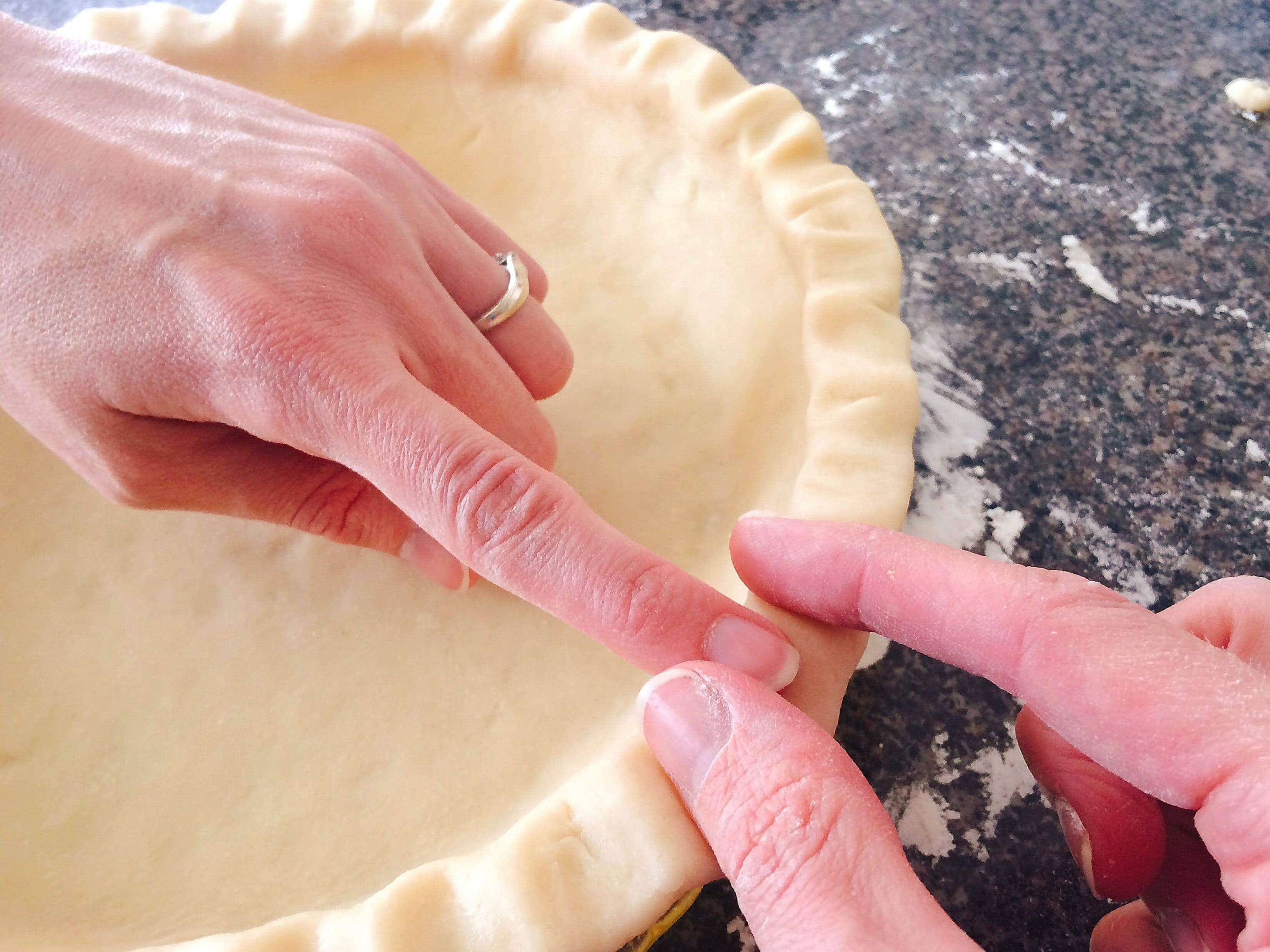 Two hands shaping a Flaky All=Butter Pie Crust in a pie pan.