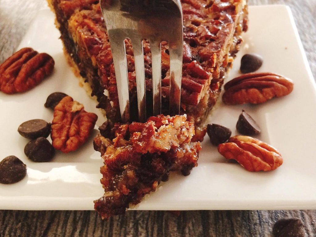A fork taking a bite out of Dark Chocolate Pecan Pie
