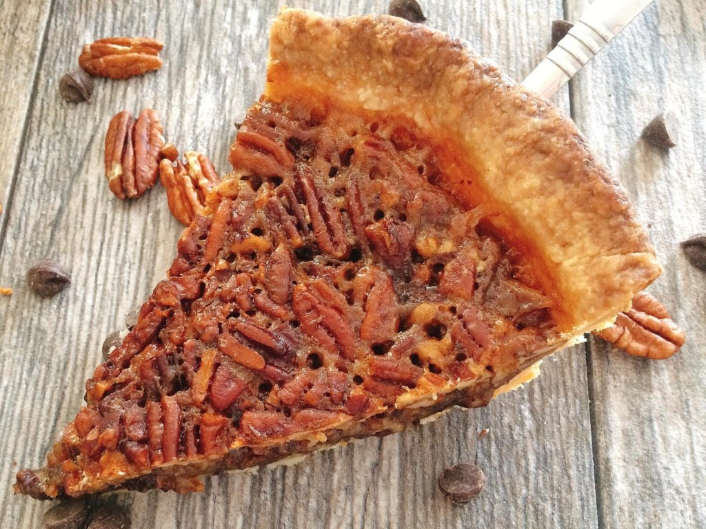 A piece of Dark Chocolate Pecan Pie with pecans and chocolate chips sprinkled around it