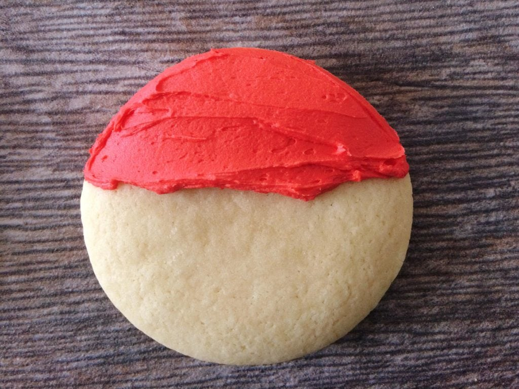 A cookie with red frosting across the top to make Santa Sugar Cookies