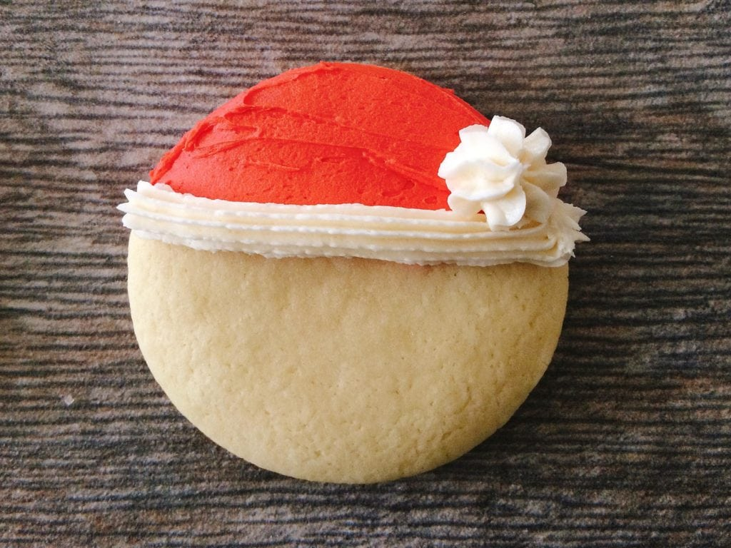 A cookie with a red and white Santa hat made of frosting to make Santa Sugar Cookies