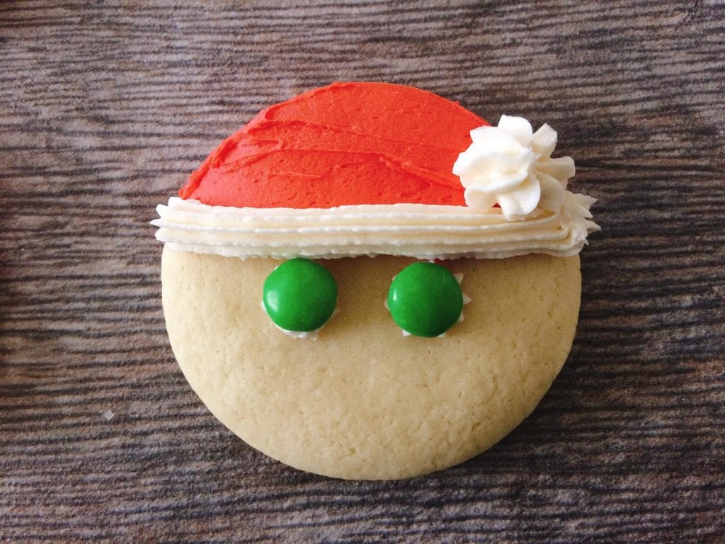 A sugar cookie with a frosting Santa hat and two green M&M's eyes to make Santa Sugar Cookies