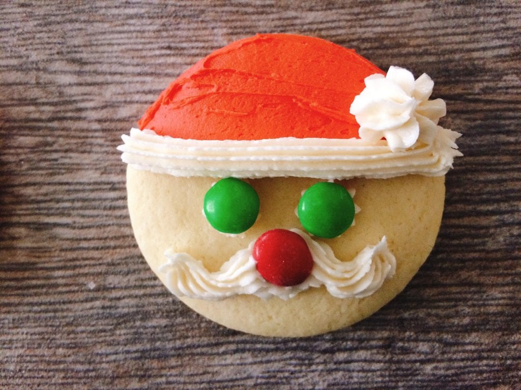 A cookie with a frosting Santa hat and mustache, green M&M's eyes and a red nose to make Santa Sugar Cookies