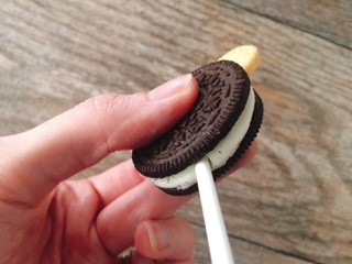 A hand holding an Oreo with a stick.