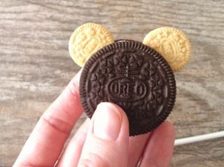 A hand holding an Oreo with two small Oreo mouse ears.