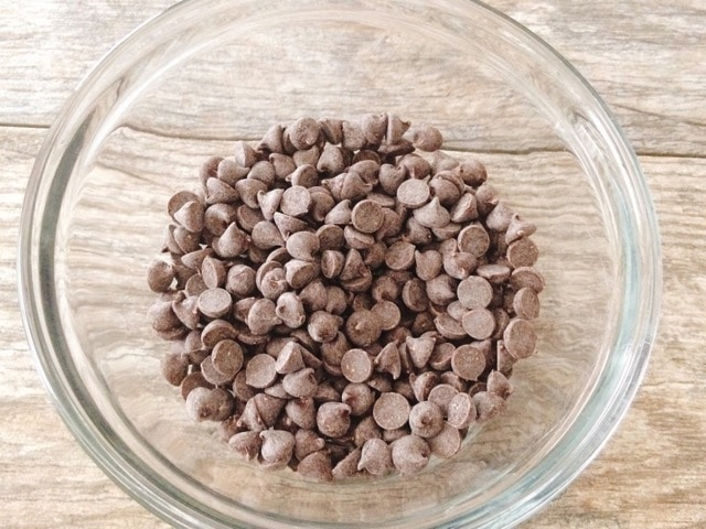 A glass bowl of chocolate chips.