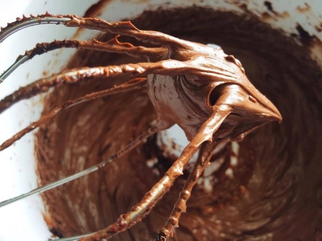 Whipped chocolate ganache on a whisk.