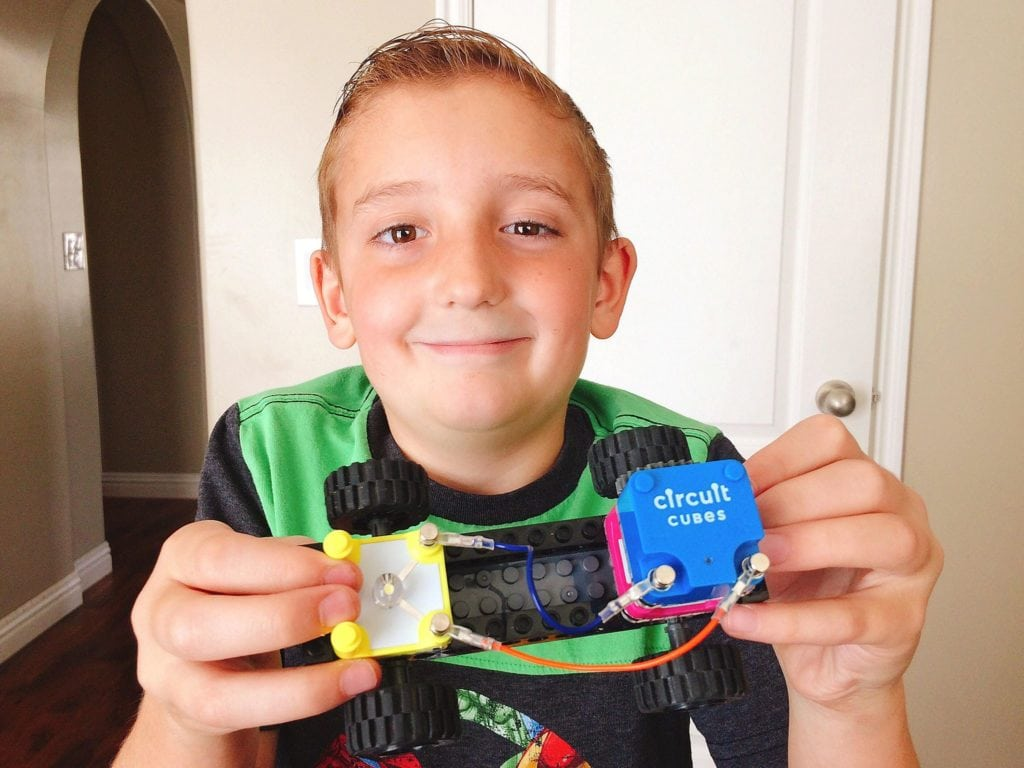 Boy holding a Circuit Cube Whacky Wheels car