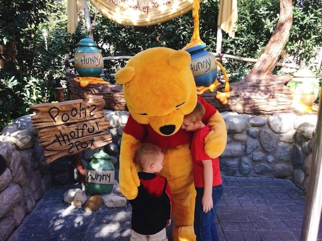 Winnie the Pooh giving two boys a hug at Disneyland. Helping them deal with Disney Withdrawl.